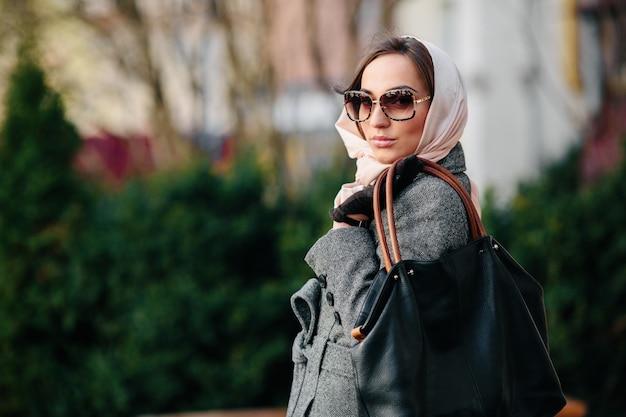 Jonge mooie gelukkige vrouw in een jas die zich voordeed in het park