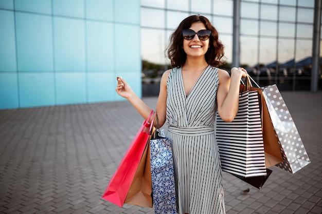 Jonge mooie gelukkige vrouw loopt uit winkelcentrum met aankopen.