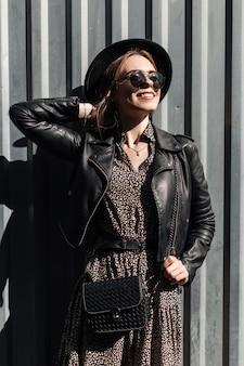 Jonge mooie gelukkige vrouw met zwarte bril in modieuze kleding met vintage jurk en leren jas met handtas in de buurt van metalen achtergrond op straat