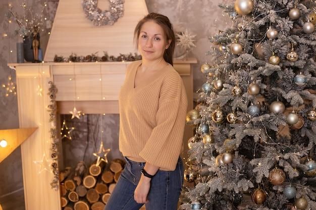 Jonge mooie gelukkige vrouw ontspannen in de buurt van de kerstboom