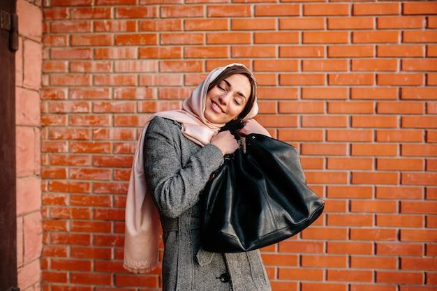 Jonge mooie gelukkige vrouw zeer tevreden met een nieuwe tas