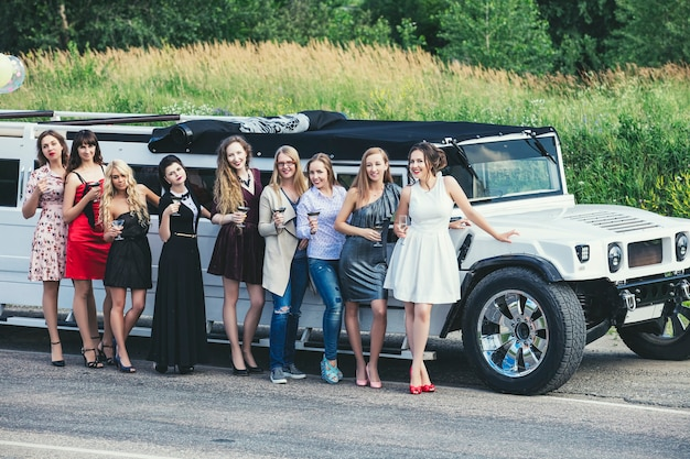 Jonge mooie gelukkige vrouwen vieren vrijgezellenfeest in een converteerbare limousine