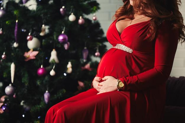 Jonge mooie gelukkige zwangere vrouw in een lange rode kleding die dichtbij nieuwe jaarboom situeert. zwangerschap en mensenconcept