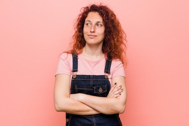 Jonge mooie gember roodharige vrouw draagt een jeans tuinbroek glimlachen vol vertrouwen met gekruiste armen