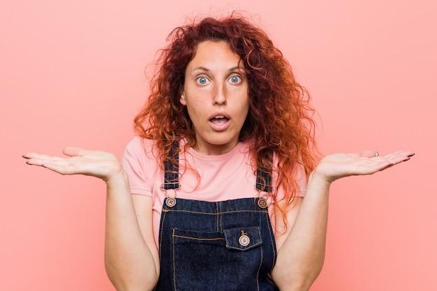 Jonge mooie gember roodharige vrouw draagt een jeans tuinbroek verrast en geschokt.