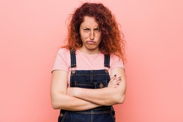 Jonge mooie gember roodharige vrouw, gekleed in een jeans tuinbroek fronsen gezicht in ongenoegen, houdt armen gevouwen.