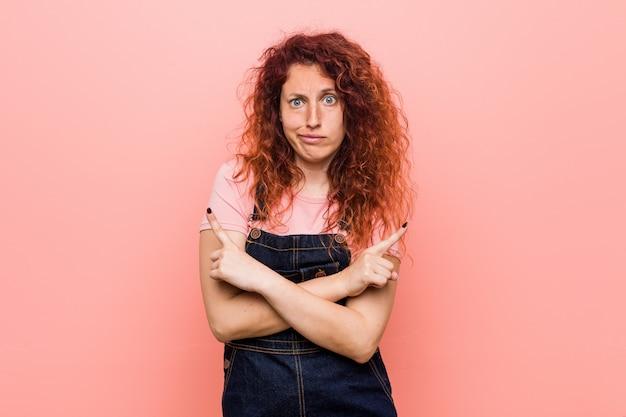 Jonge mooie gember roodharige vrouw, gekleed in een jeans tuinbroek punten zijwaarts, probeert te kiezen tussen twee opties.