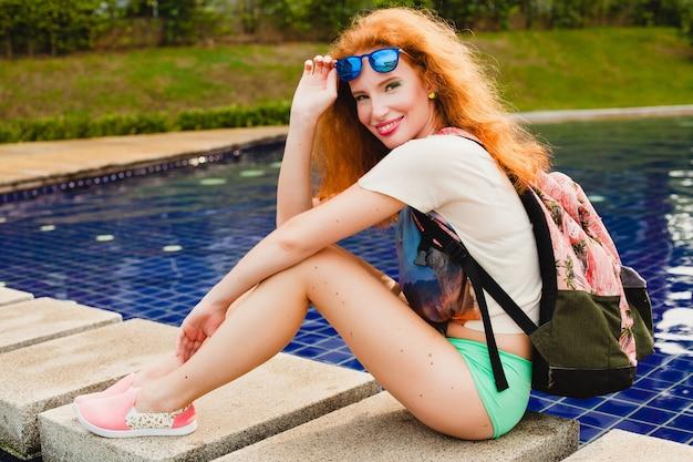 Jonge mooie gember vrouw zitten bij zwembad met rugzak, ontspannen, gelukkig, zomer, coole hipster outfit, korte broek, t-shirt, sneakers, zonnebril