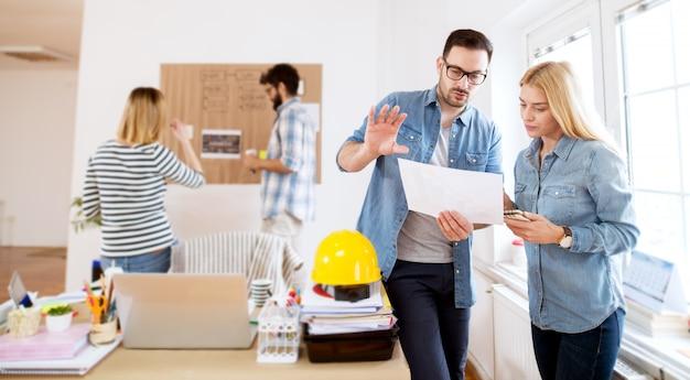 Jonge mooie gerichte succesvolle bedrijfsmensen die creatieve ideeën delen en samen plannen op kantoor.