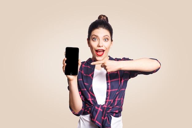 Jonge mooie geschokte vrouw in casual stijl met telefoon die naar de camera kijkt en de telefoon weergeeft. studio-opname op beige achtergrond.