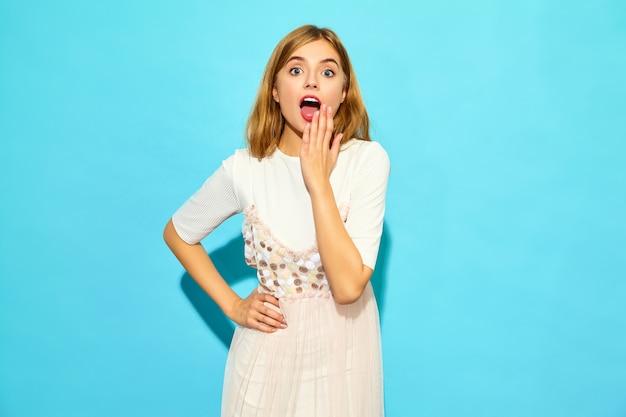 Jonge mooie geschokte vrouw. trendy vrouw in casual zomerkleding. grappig model dat op blauwe muur wordt geïsoleerd