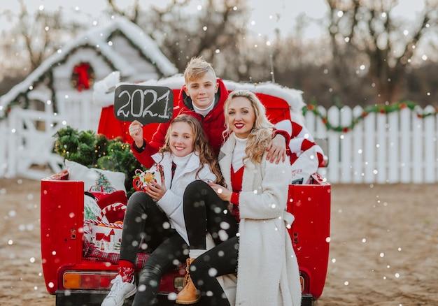 Jonge mooie gezin van drie in rode en witte winterkleren poseren in rode open retro auto met kerstboom en naamplaatje met 2021-teken onder het sneeuwt.