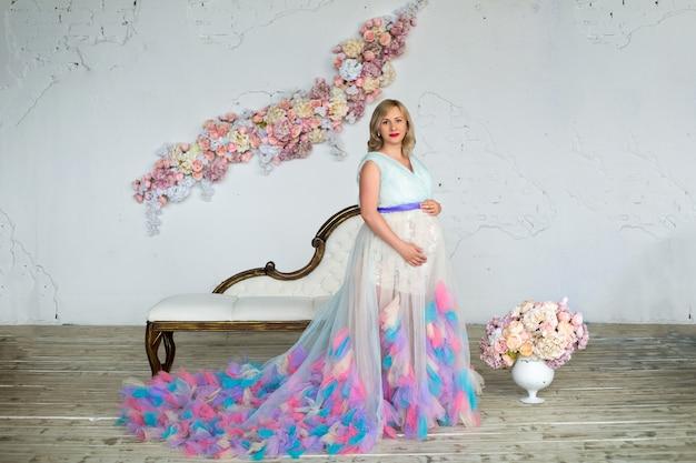 Jonge mooie glamour zwangere vrouw in een kleurrijke gezwollen jurk staat in een bloemenzolder. gelukkig zwangerschap