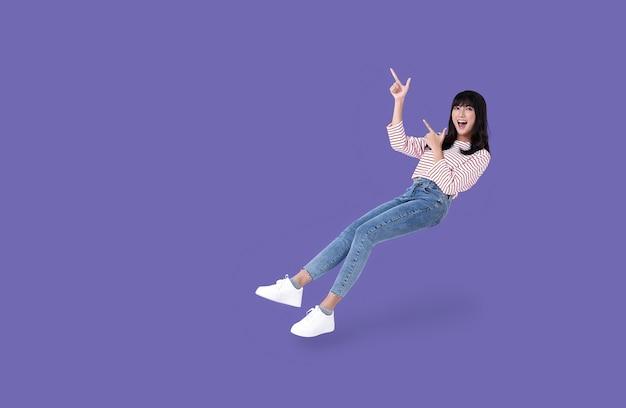 Jonge mooie glimlachende aziatische meisjeshand die omhoog wijst om ruimte op paars te kopiëren.