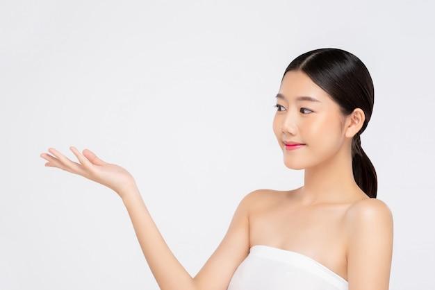 Jonge mooie glimlachende aziatische vrouw die open hand voor schoonheidsconcepten uitdrukken