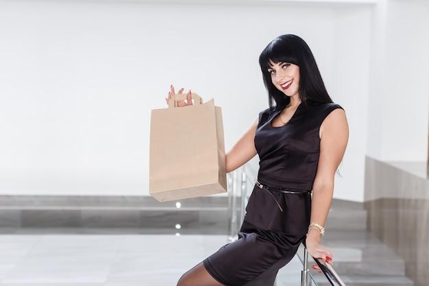 Jonge mooie glimlachende brunette vrouw met papieren boodschappentas, lopen op een winkelcentrum.