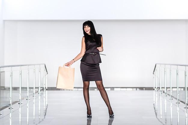 Jonge mooie glimlachende brunette vrouw met papieren boodschappentas, wandelen in een winkelcentrum.