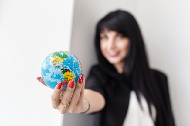 Jonge mooie glimlachende donkerbruine vrouw die een bol van de aarde houdt.