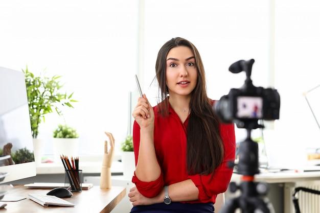 Jonge mooie glimlachende donkerbruine vrouw in rode blousezitting in bureau tegenover camera op statief en de voorstellende diensten. bedrijfsdame, secretaresse, mensen in bureauconcept