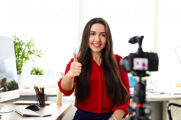 Jonge mooie glimlachende donkerbruine vrouw in rode overhemdszitting in bureau tegenover camera op driepoot en het tonen van de goede vinger van de gelukduim. bedrijfsdame, secretaresse, mensen in bureauconcept
