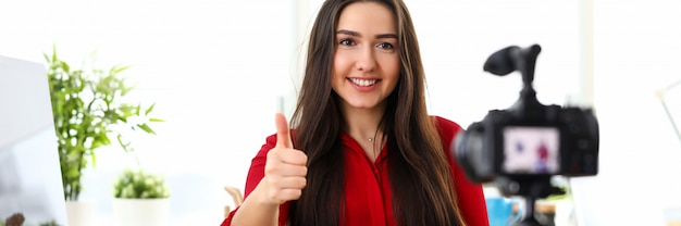 Jonge mooie glimlachende donkerbruine vrouw in rode overhemdszitting in bureau tegenover camera op driepoot en het tonen van de goede vinger van de gelukduim.