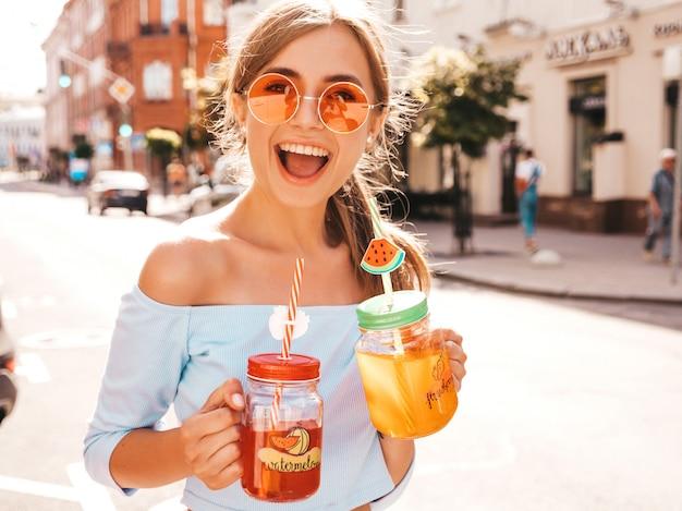 Jonge mooie glimlachende hipster vrouw in zonnebril.