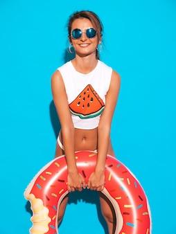 Jonge mooie glimlachende sexy vrouw in zonnebril. meisje in witte zomeronderbroek en onderwerp met de opblaasbare matras van doughnutlila.