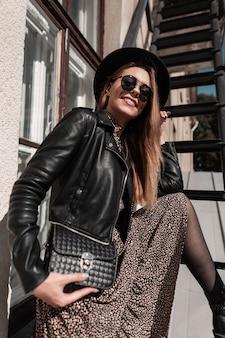 Jonge mooie glimlachende stijlvolle vrouw met zonnebril en hoed in zwarte jas en vintage jurk met handtas in handen poses op straat op zonnige dag