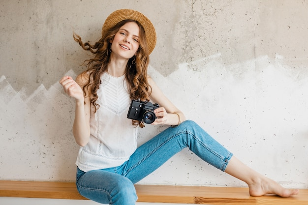 Jonge mooie glimlachende vrouw die blauwe denimjeans en wit overhemd draagt die tegen muur in strohoed zitten