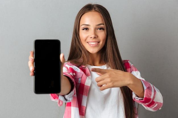 Jonge mooie glimlachende vrouw die met vinger op het telefoonscherm richt