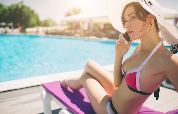 Jonge mooie glimlachende vrouw in bikini in warm zwembad bij de toevlucht en bespreking in mobiele telefoon.
