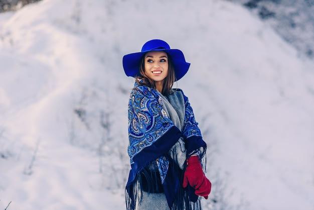 Jonge mooie glimlachende vrouw in blauwe muts en sjaal