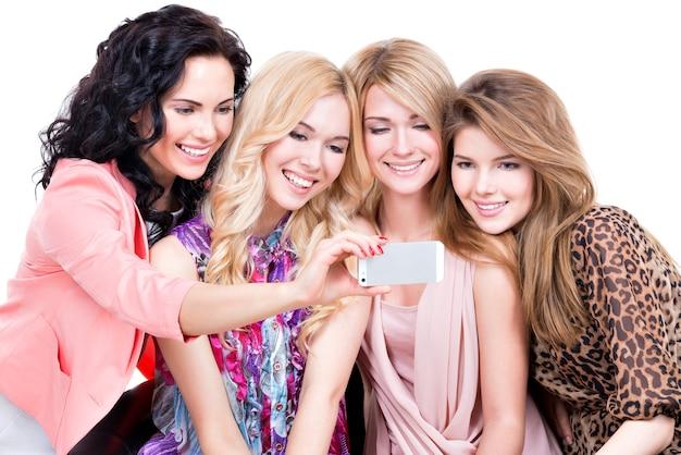 Jonge mooie glimlachende vrouwen die de geïsoleerde mobiele telefoon bekijken -
