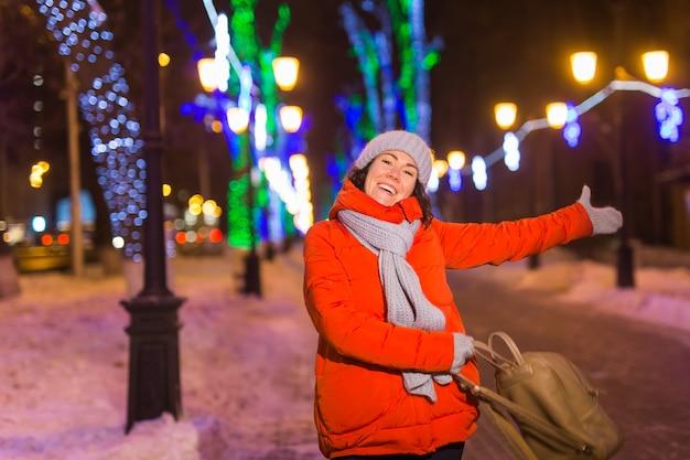 Jonge mooie grappige meid met plezier buiten in de winter kerststad en wintervakantie concept