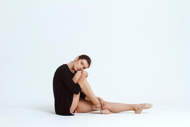 Jonge mooie hedendaagse danser poseren over witte muur