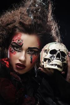 Jonge mooie heks die een schedel over dark houdt