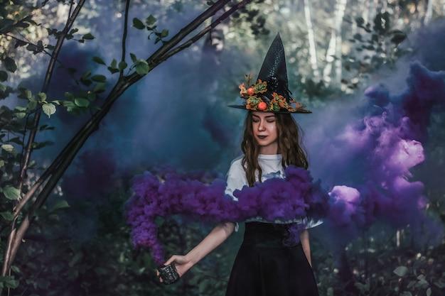 Jonge mooie heks in zwarte hoed en met paarse mist in haar hand close-up in het bos.