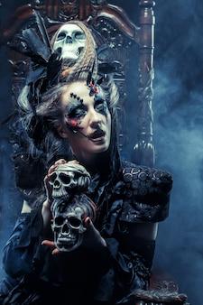 Jonge mooie heks zit op een stoel. lichte make-up, schedel, rook-halloween-thema.