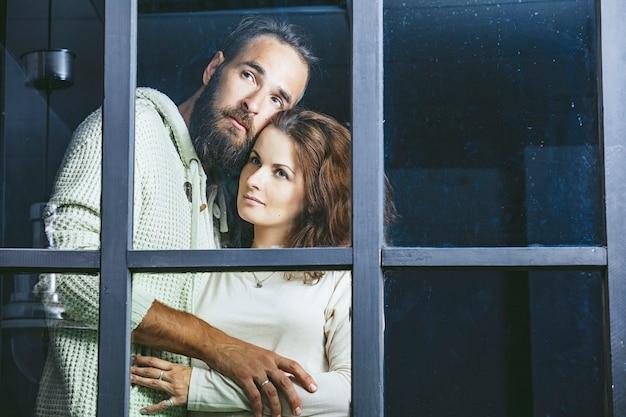 Jonge mooie heteroseksuele paar man en vrouw liefhebbers omhelzen buiten het raam