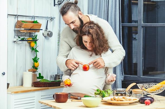 Jonge mooie heteroseksuele paar man en vrouw liefhebbers zwanger in de keuken thuis koken