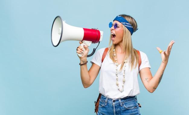Jonge mooie hippievrouw met een leerzak en een megafoon