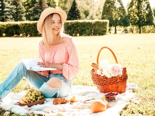 Jonge mooie hipster meisje in trendy zomerjeans, roze t-shirt en hoed. zorgeloze vrouw die buiten picknick maakt.