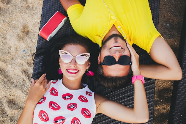 Jonge mooie hipster paar verliefd, liggend omhelzen, luisteren naar muziek, zonnebril, stijlvolle outfit, zomervakantie, plezier hebben, glimlachen, gelukkig, kleurrijk, van bovenaf bekijken