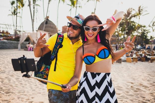 Jonge mooie hipster paar verliefd op tropisch strand, selfie foto nemen op smartphone, zonnebril, stijlvolle outfit, zomervakantie, plezier hebben, glimlachen, gelukkig, kleurrijk, positieve emotie