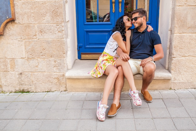 Jonge mooie hipster paar verliefd zittend op oude stad straat