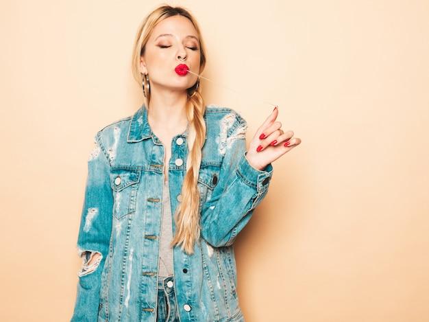 Jonge mooie hipster slecht meisje in trendy jeans kleding en oorbel in haar neus. positief model dat pret heeft. zij trekt een kauwgom