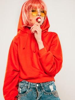 Jonge mooie hipster slecht meisje in trendy rode zomer rode hoodie en oorbel in haar neus. sexy zorgeloze vrouw poseren in studio op grijze achtergrond in pruik. heet model likken rond suikersuikergoed