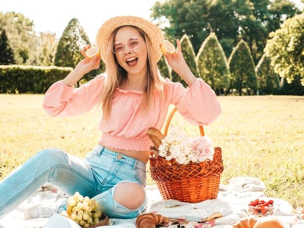 Jonge mooie hipster vrouw in trendy zomerjeans, roze t-shirt en hoed. vrouw die buiten picknick maakt.