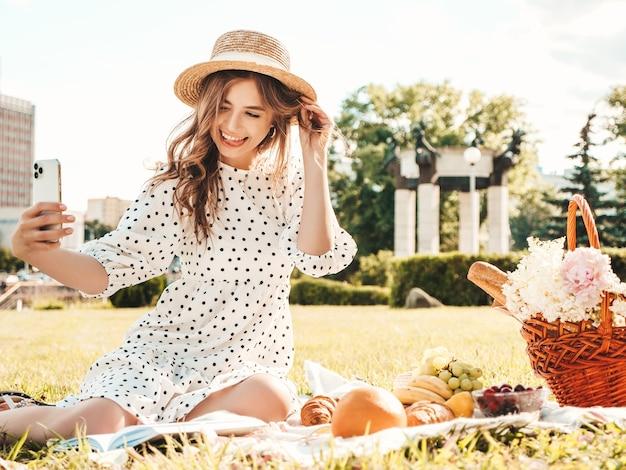Jonge mooie hipster vrouw in trendy zomerjeans, roze t-shirt en hoed. zorgeloze vrouw die buiten picknick maakt.