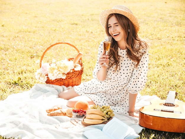 Jonge mooie hipster vrouw in trendy zomerjurk en hoed. zorgeloze vrouw die buiten picknick maakt.
